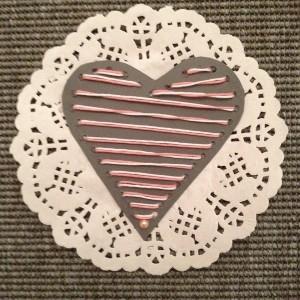 Ett hjärta som är sytt i papper och klistrat på ett minikakunderlägg