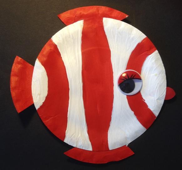 En röd- och vitrandig fisk målad på en papptallrik