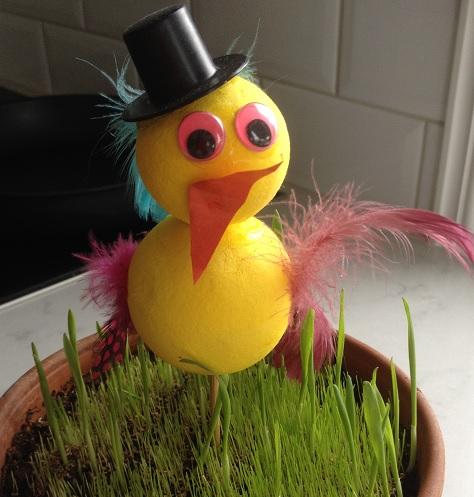 En kyckling av flirtkulor i dekorationsgräs